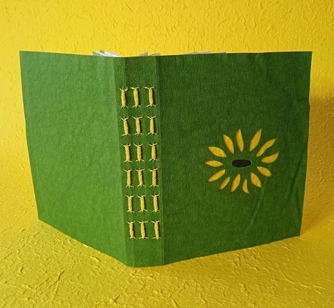 green book cover with flower cut out