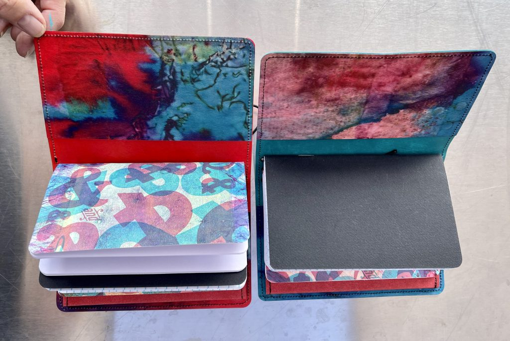 two decorated Kraft-tex book covers with splashes of red and blue opened up to see pages inside