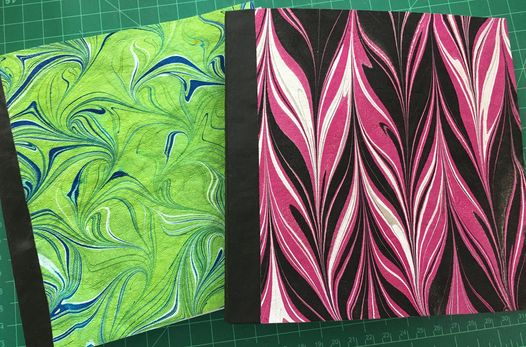 marbled Kraft-tex book covers, one in green and blue and one in pink and black