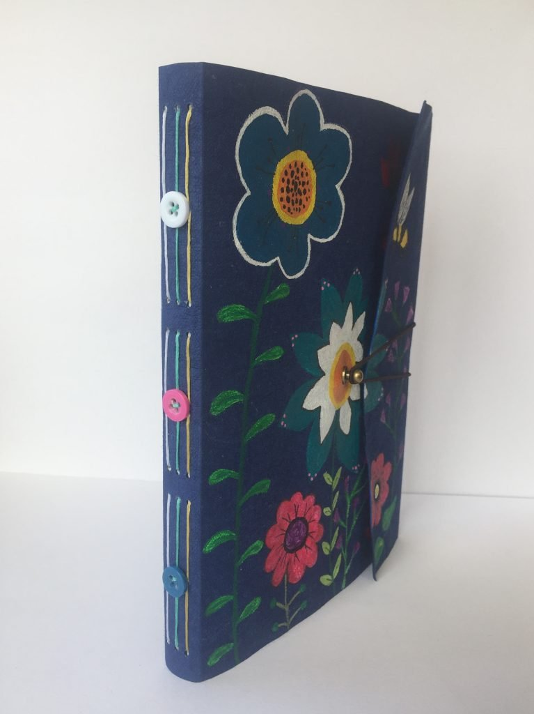 purple book cover with paintings of flowers and bees and long stitch on spine